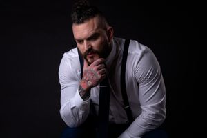 Tattooed male model wearing white shire and tie poses with hand on chin