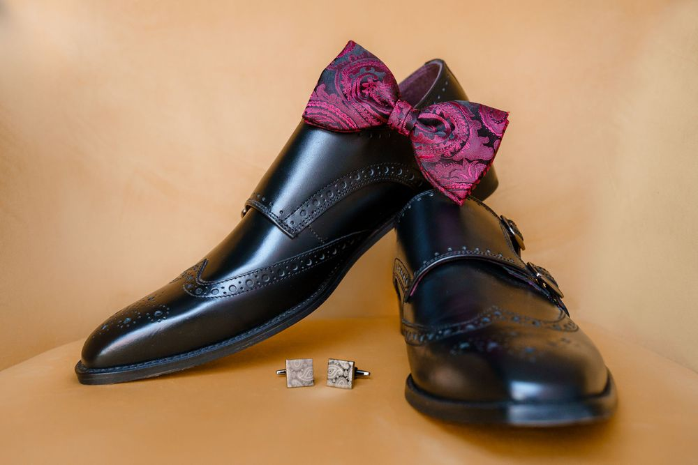 Men's black wedding shoes with a burgundy bow tie and cufflinks on a yellow velvet chair - Hampshire wedding photography
