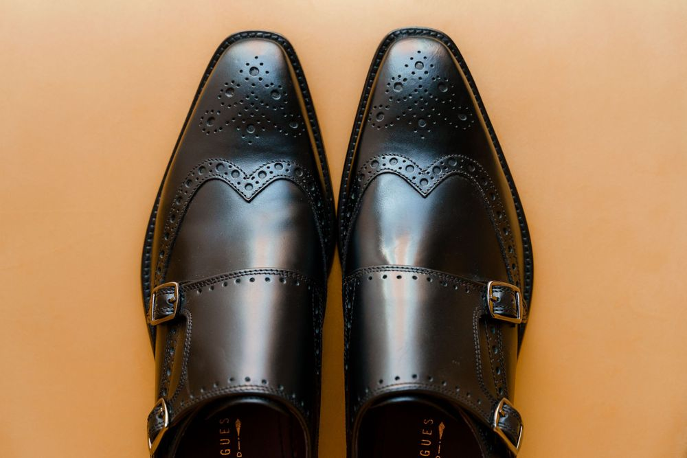 Black men's dress shoes on a yellow velvet background - Hampshire wedding photography