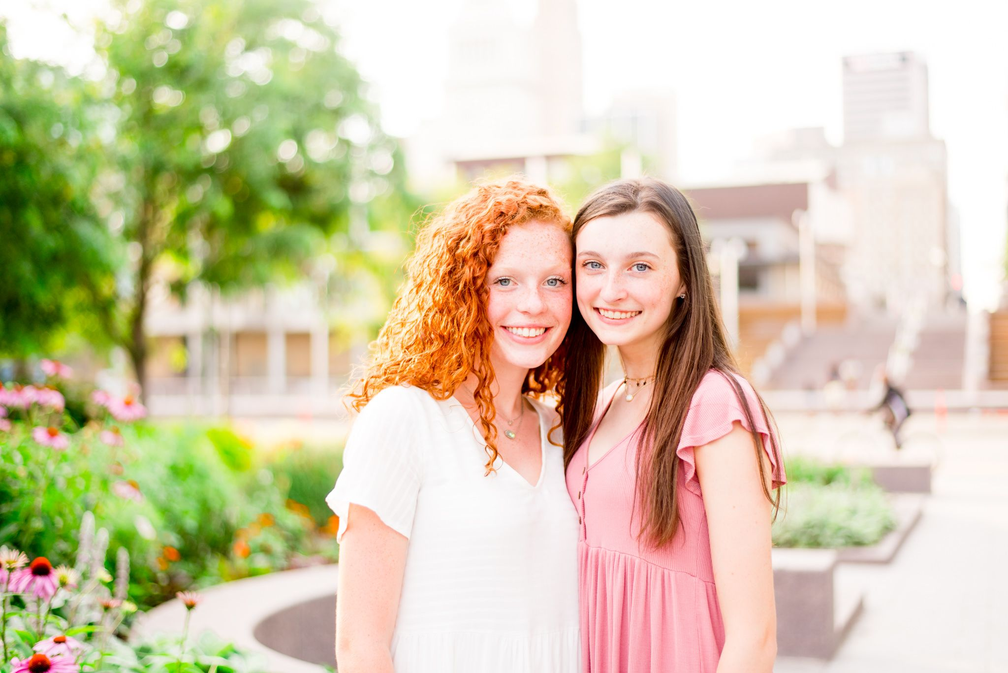 two teenage girls with red hair and brown hair stand together smiling in Smale Park at sunset