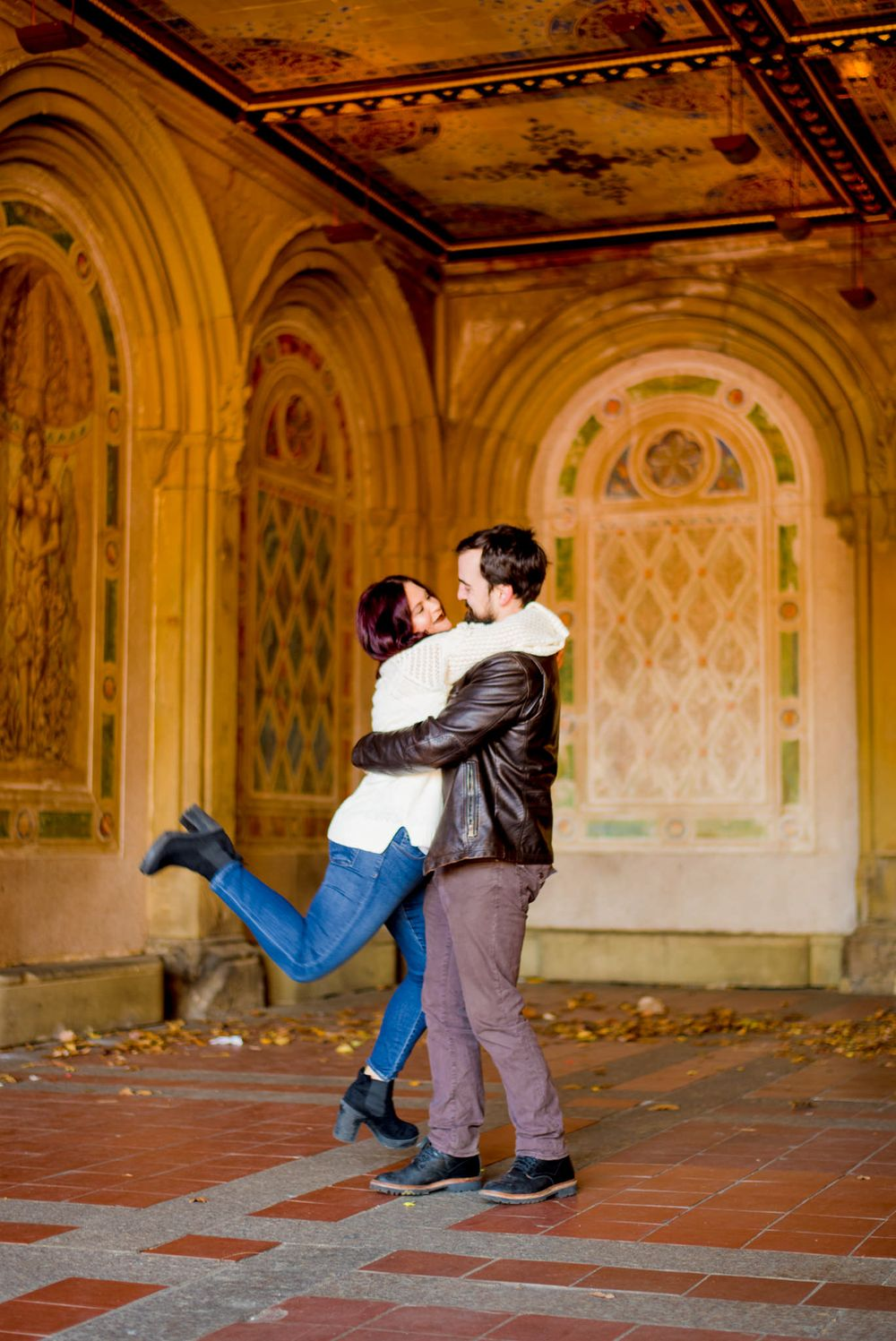 young woman hugging man and kicking feet up at Bethesda Terrace in Central Park for engagement pictures