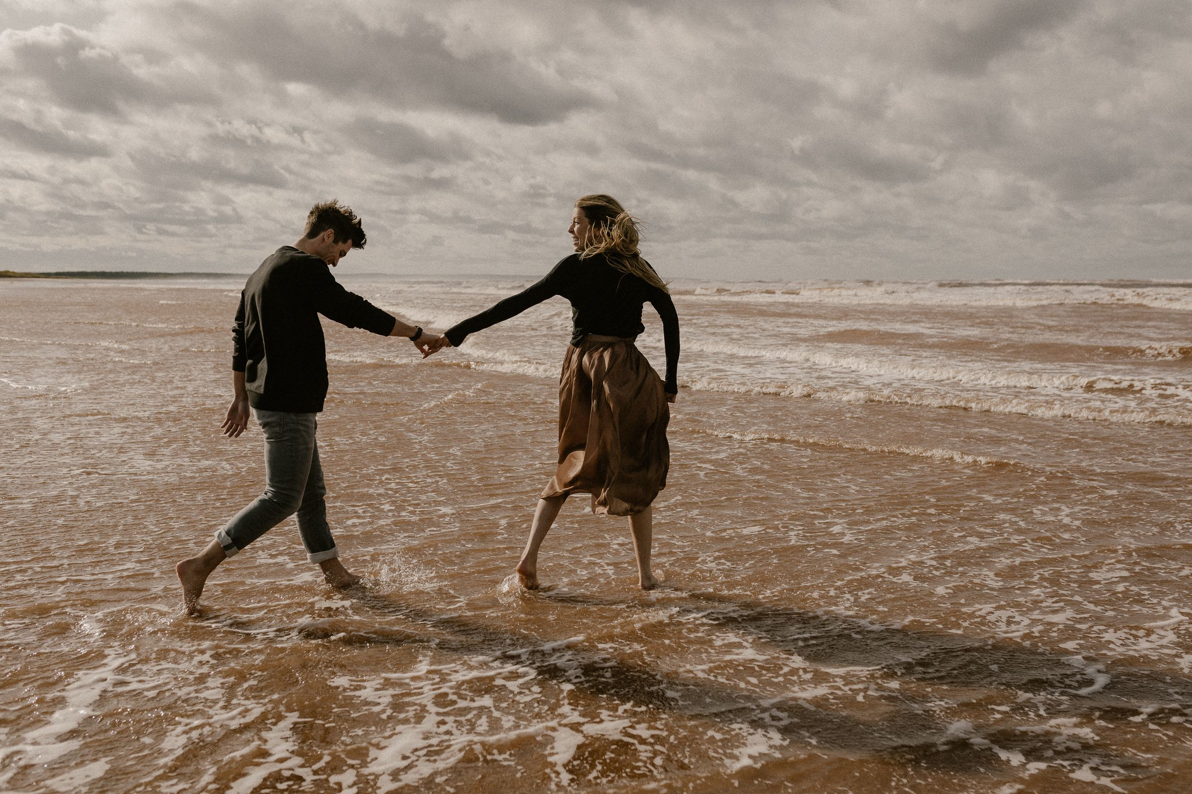 Couple at PEI beach holding hands looking back at each other and walking in the waves.