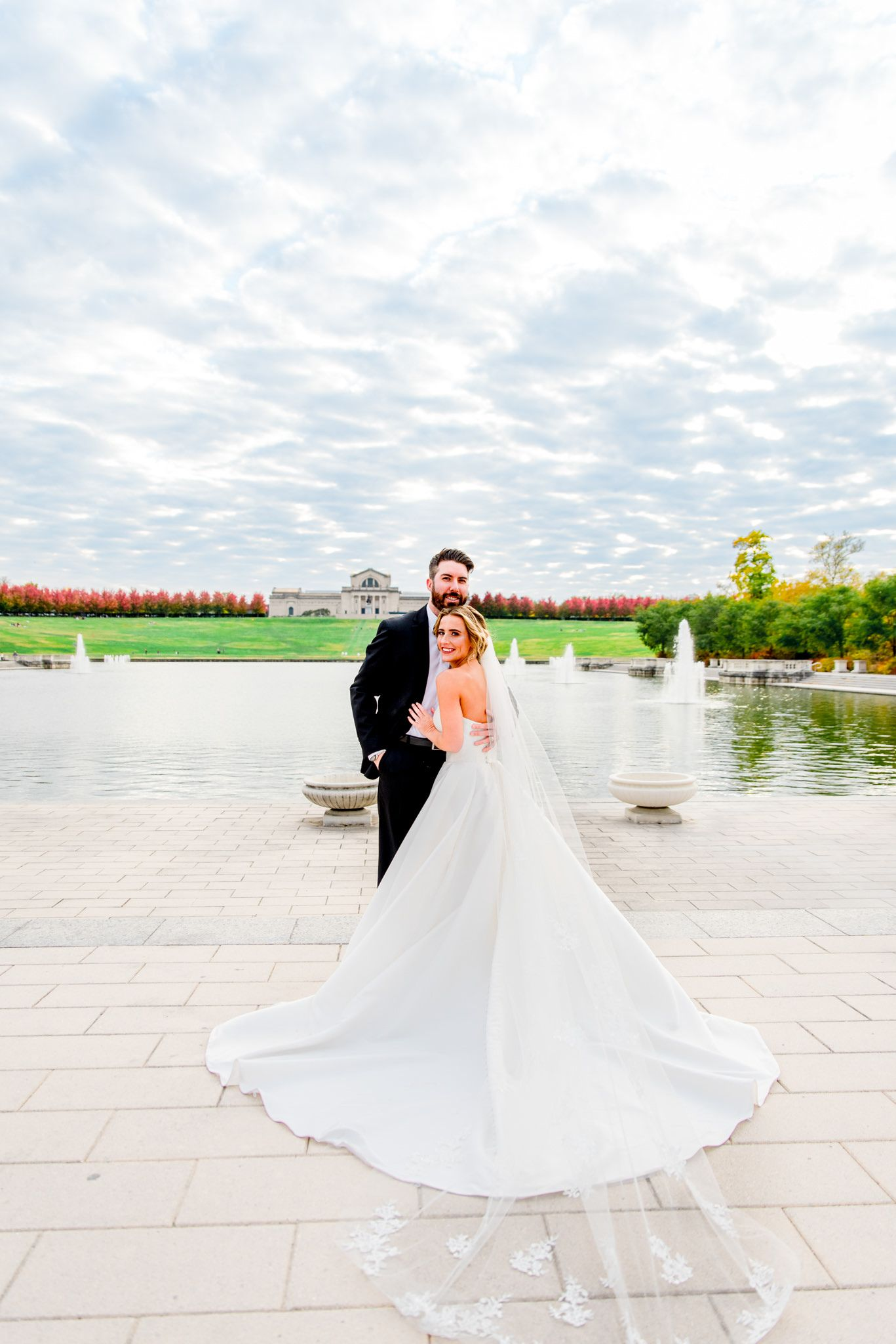 bride's wedding dress and veil fanned out next to groom under blue sky with clouds for Forest Park STL fall wedding