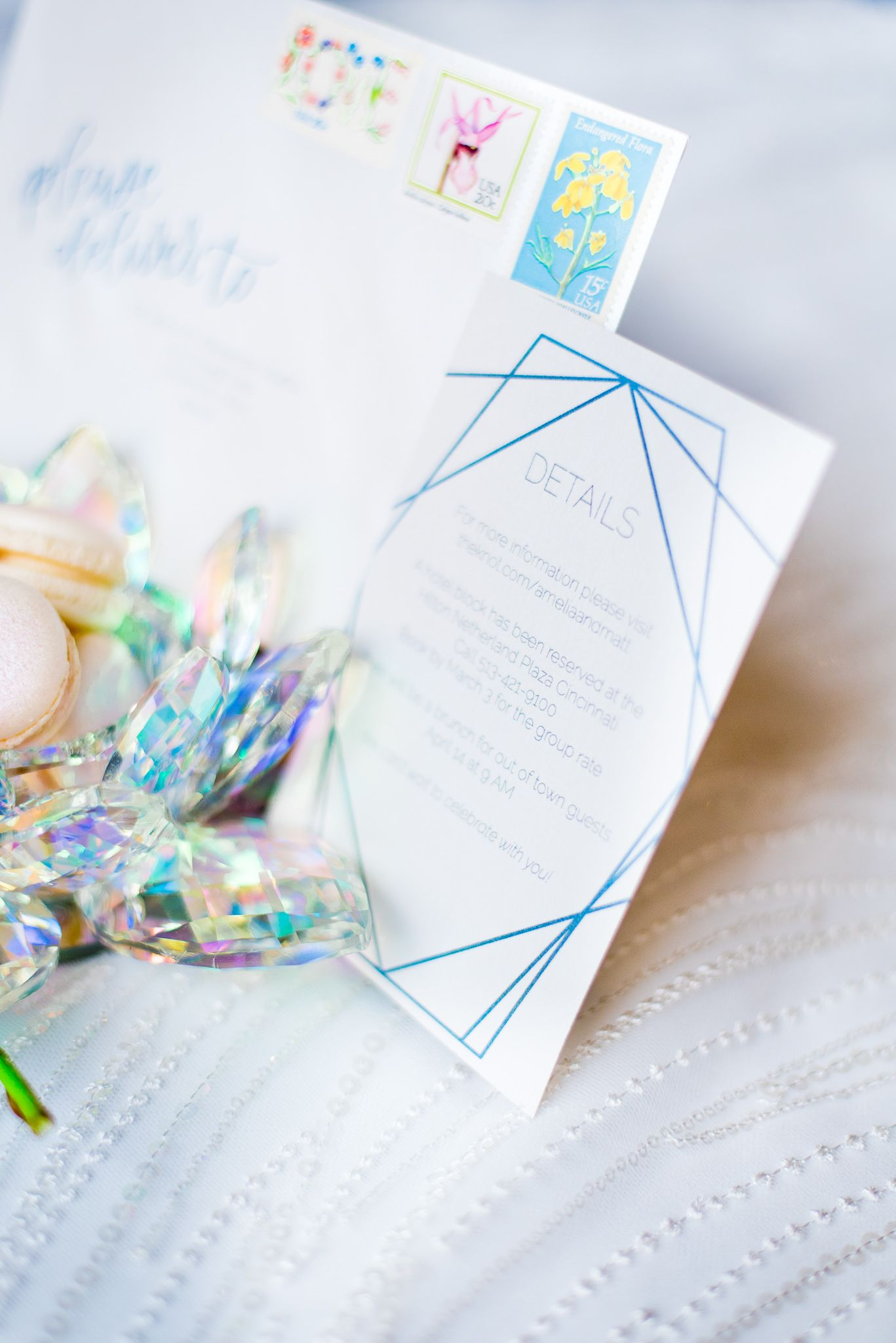 close up of blue and white wedding invitation next to a rainbow crystal bowl for a wedding at The Center Cincinnati
