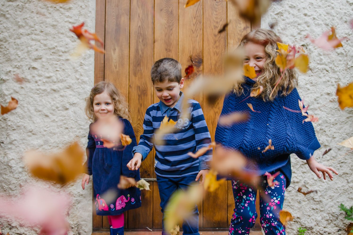 photograph of cousins throwing leaves