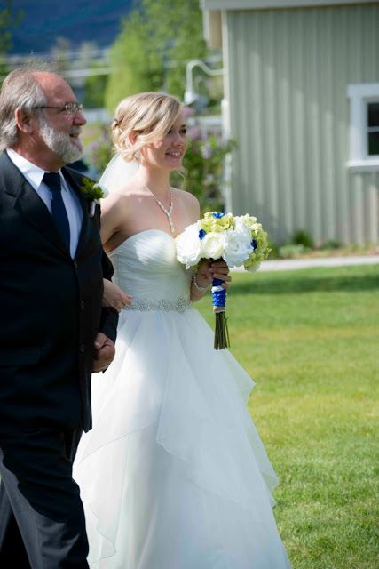 bride and dad walking to ceremony outside