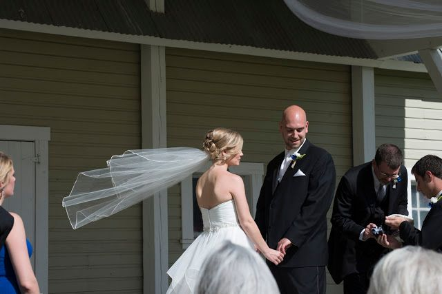 bride and groom at ceremony, bride's vail blown by wind