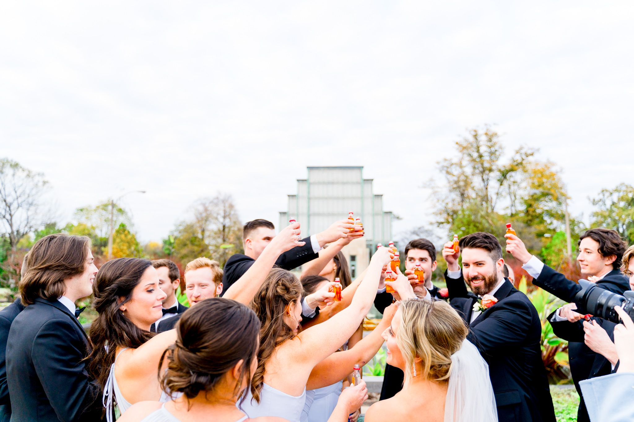 large wedding party clinking together shot bottles of Fireball for fall wedding in STL