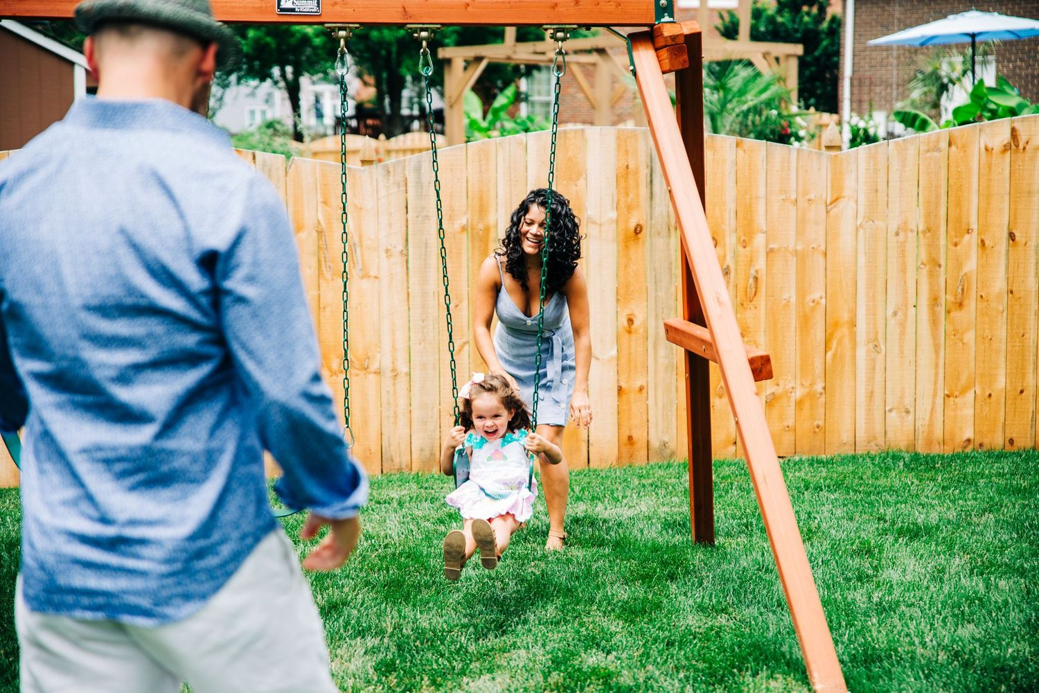 Parents pushing daughter on swings during Charlotte, NC family photo session