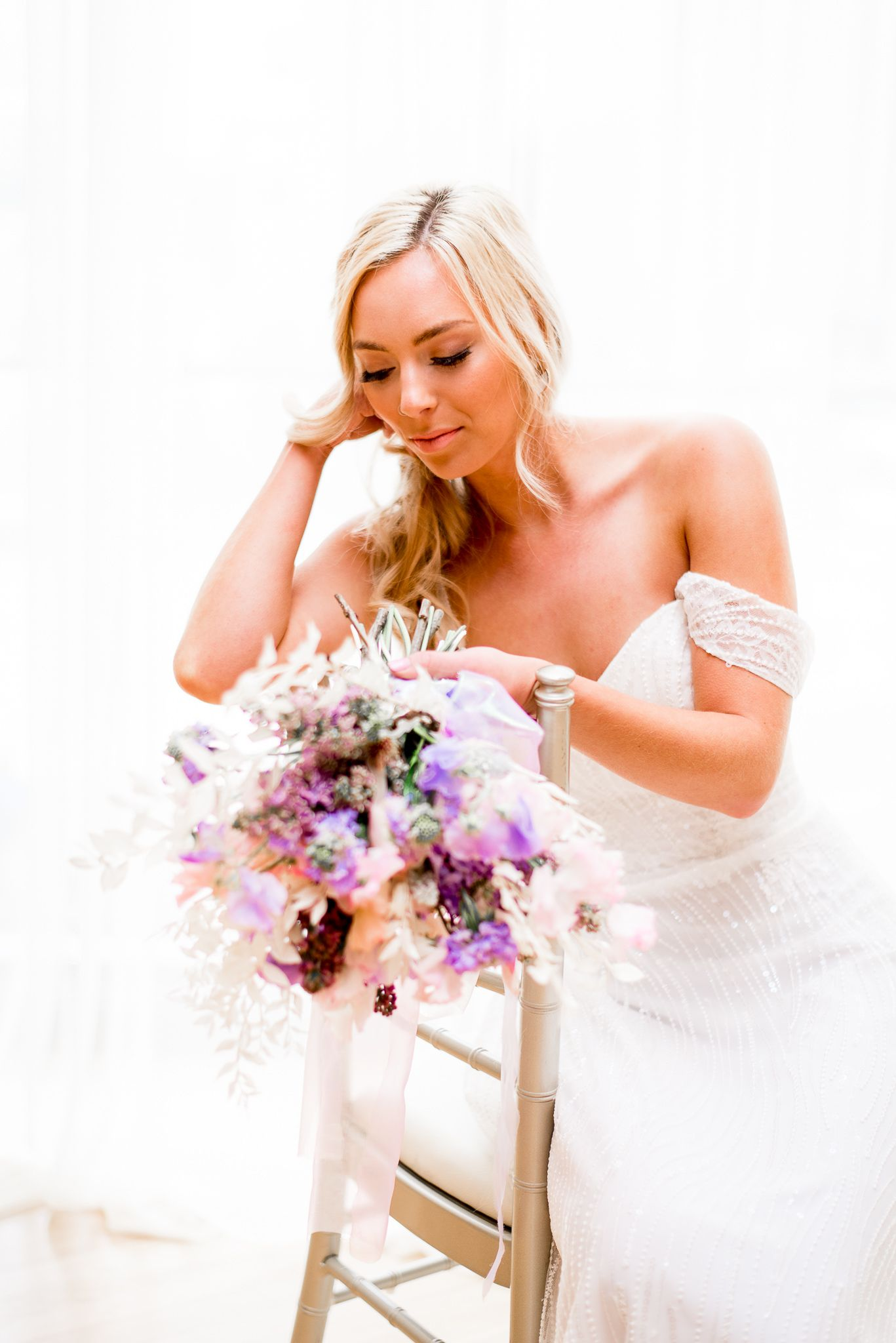 blonde bride looking at her pink and purple wedding flowers at The Center Cincinnati