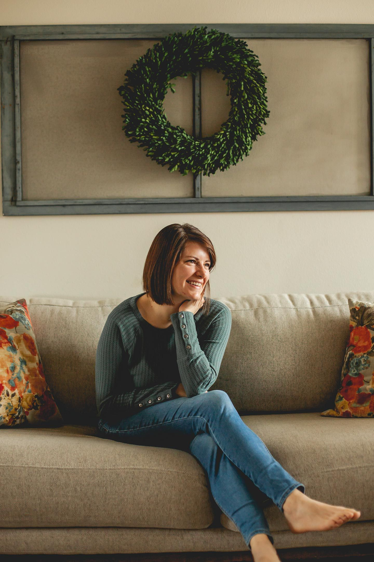 a woman sitting on her living room couch and smiling towards the natural light coming in her window