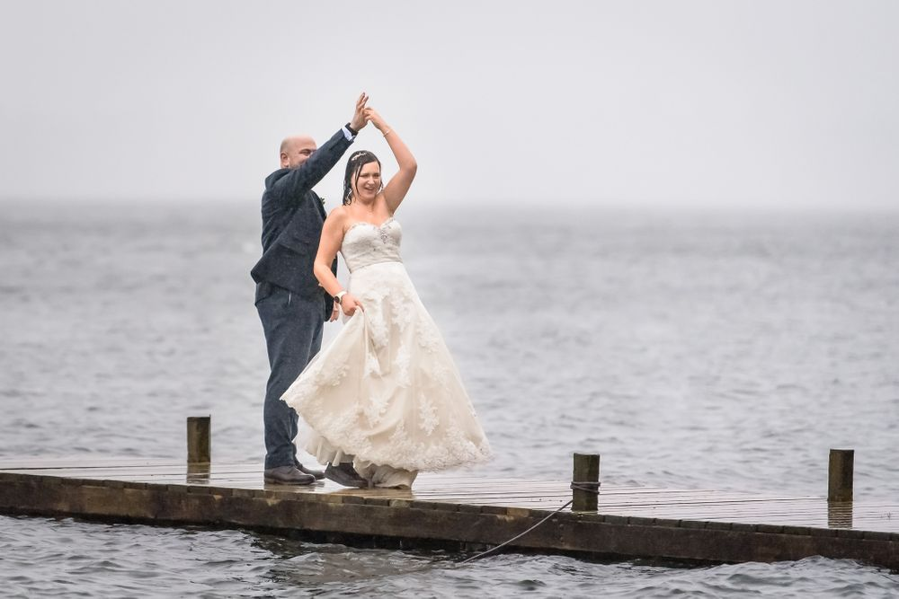 Wedding couple dancing in rain on jetty at Windermere