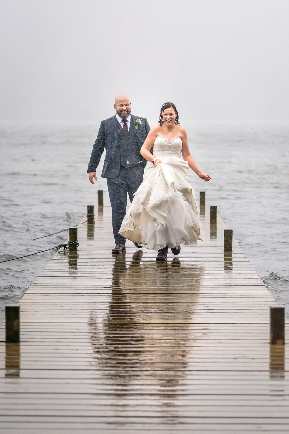 Bride and groom walk along jetty in rain at Windermere