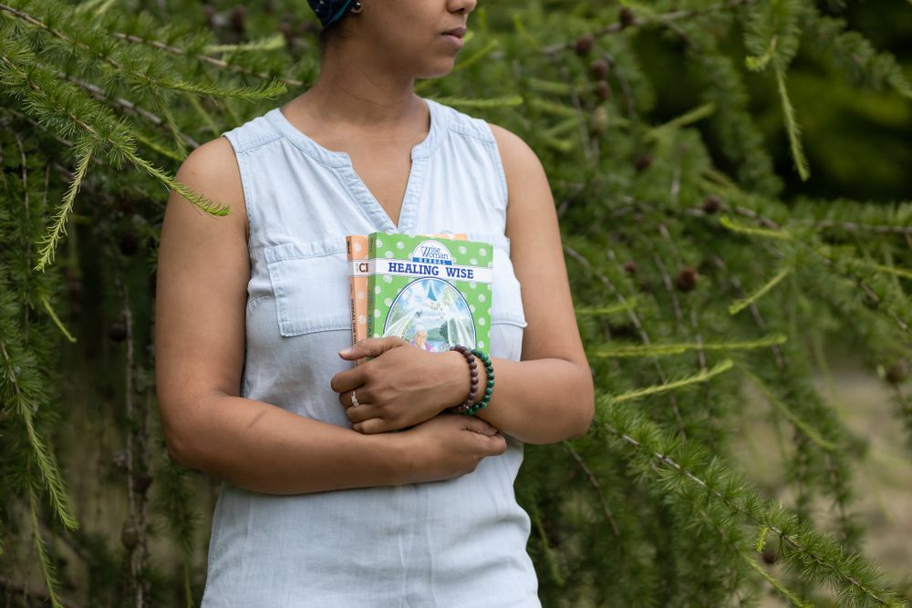 PNW Apothecary black female owner hold midwife books by tree