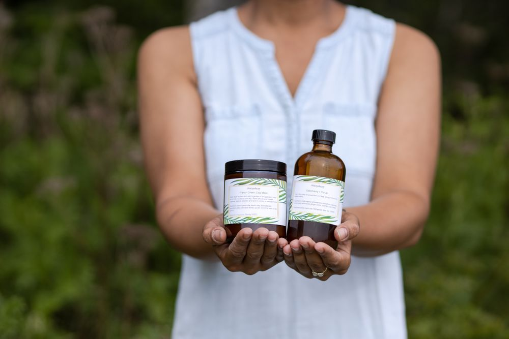 PNW Apothecary black female owner holding handmade products