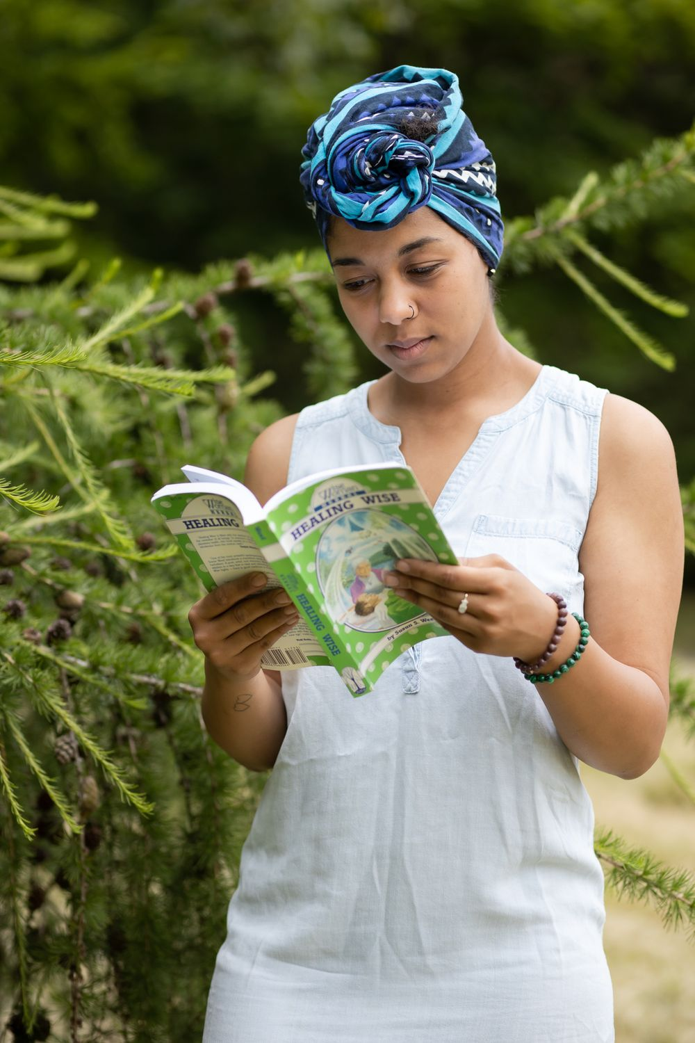 PNW Apothecary black female owner reading midwife books by tree