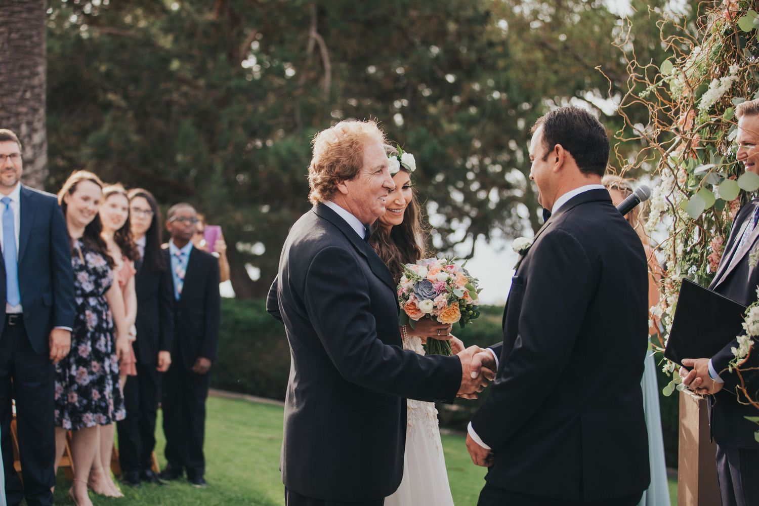father shaking grooms hand