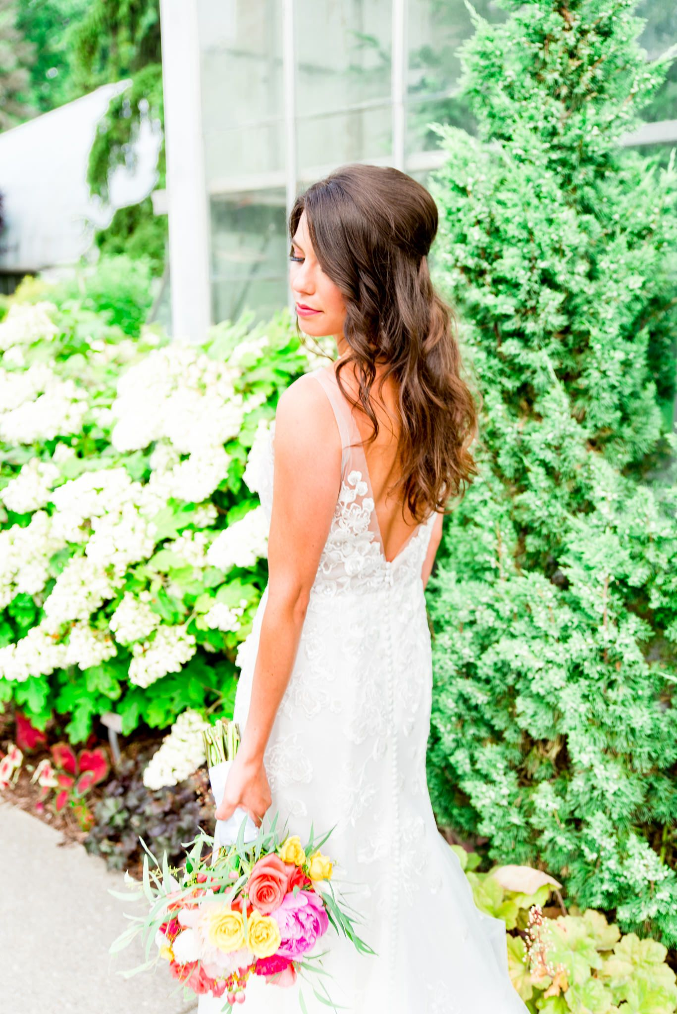 brown hair bride with loose curls and half up do holding bouquet in front of juniper tree at Krohn Conservatory