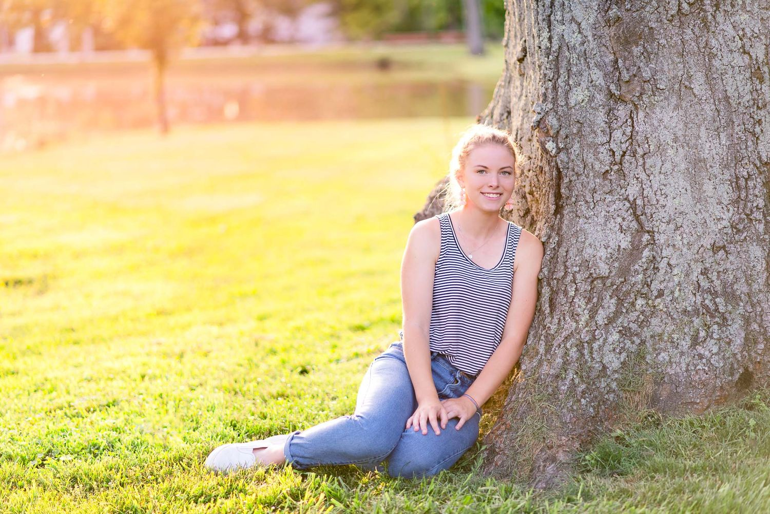 blonde young woman leaning against big tree trunk at sunset in Cincinnati Ohio