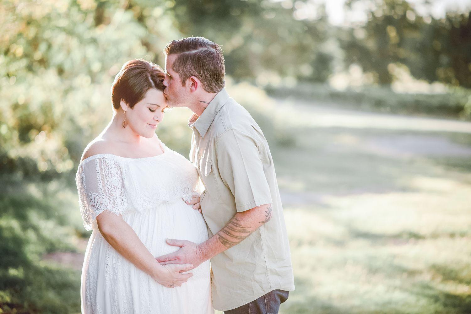 Husband kisses pregnant wife at their maternity session at Arrington Vineyards