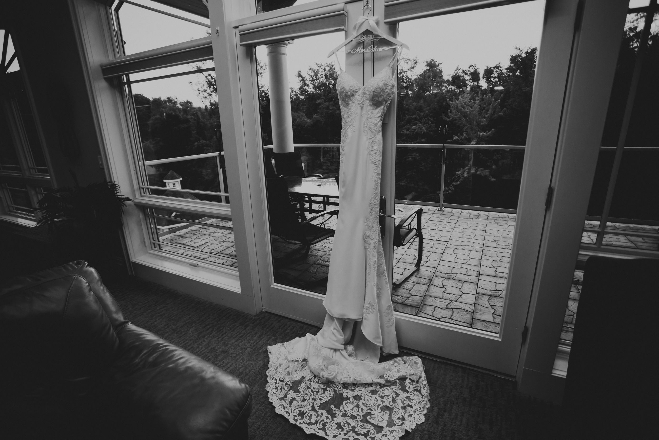Black and white photo of thin lacey wedding gown hanging in a large window.