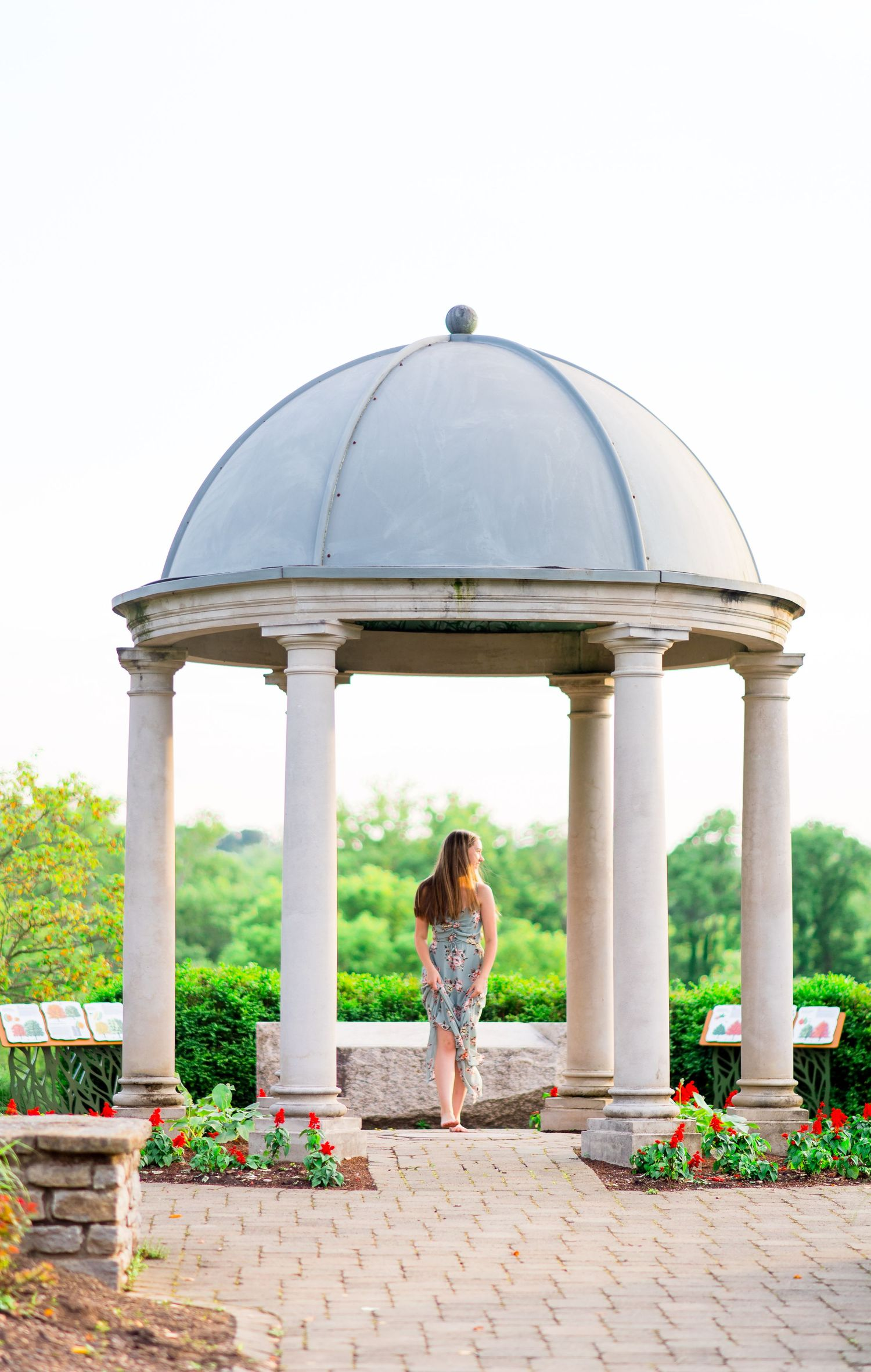 girl looks to the side under gazebo for summer senior pictures at sunset in Chicago