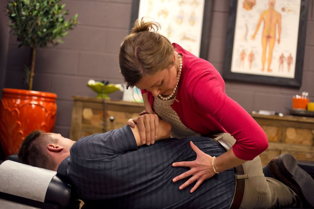 Adjusting male client back Chiropractic & Health