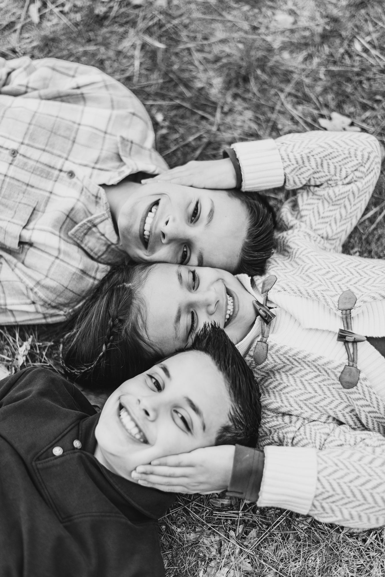 Family session with siblings in black and white lying on ground at North Park, Pittsburgh, Pennsylvania