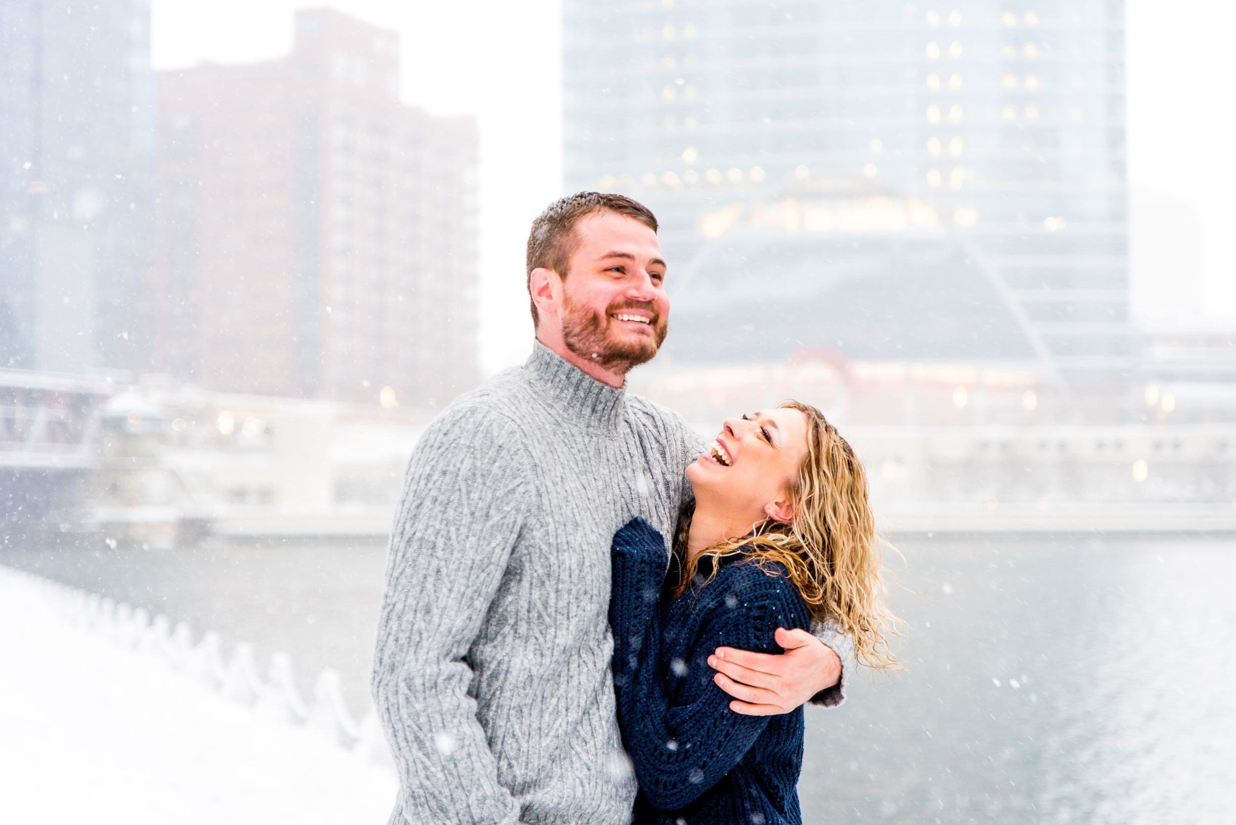 man and woman in navy and grey sweaters smiling in snow at Wolf Point Chicago
