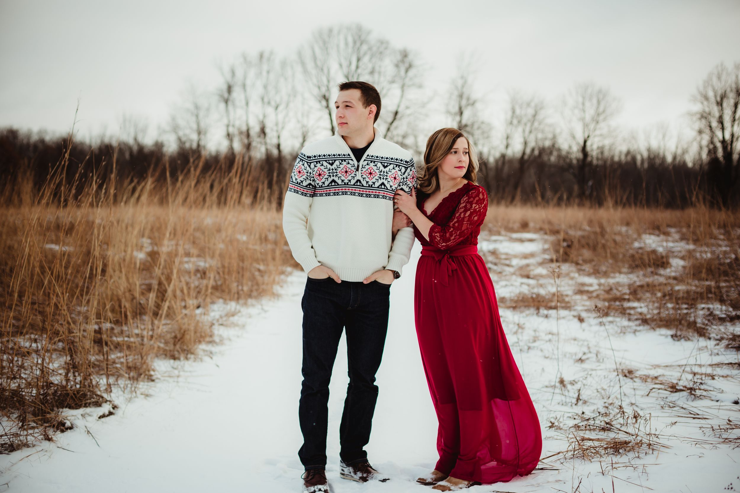 A woman holding a man's arm looking opposite directions. It is winter and she has a long red dress.