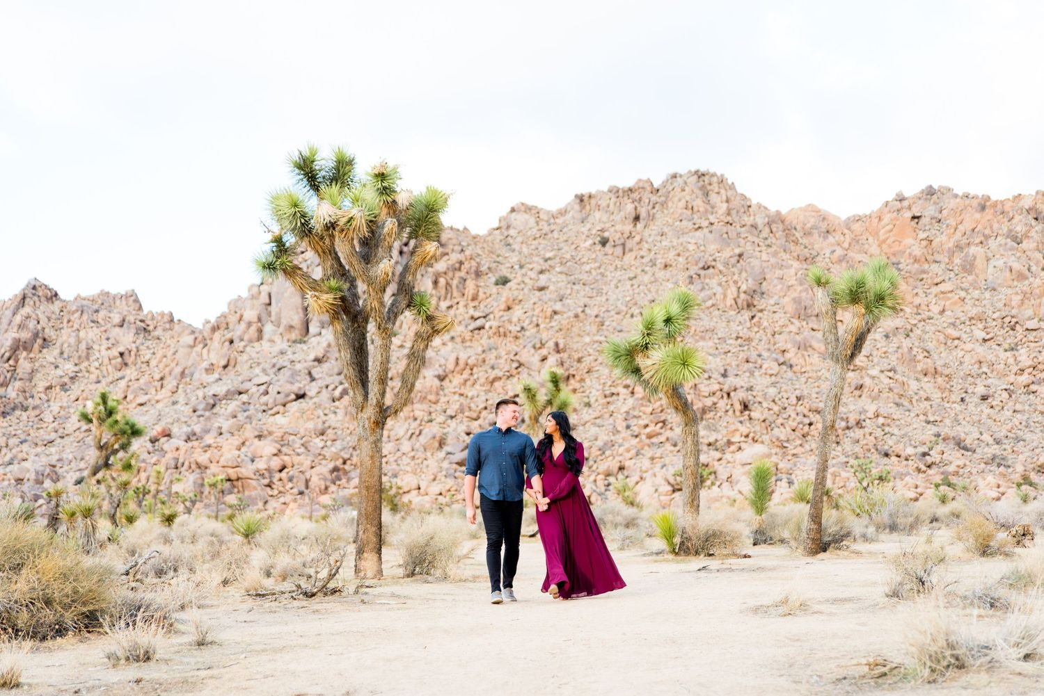 woman in red dress and man in blue shirt smiling and walking through Joshua Tree National Park for engagement pictures