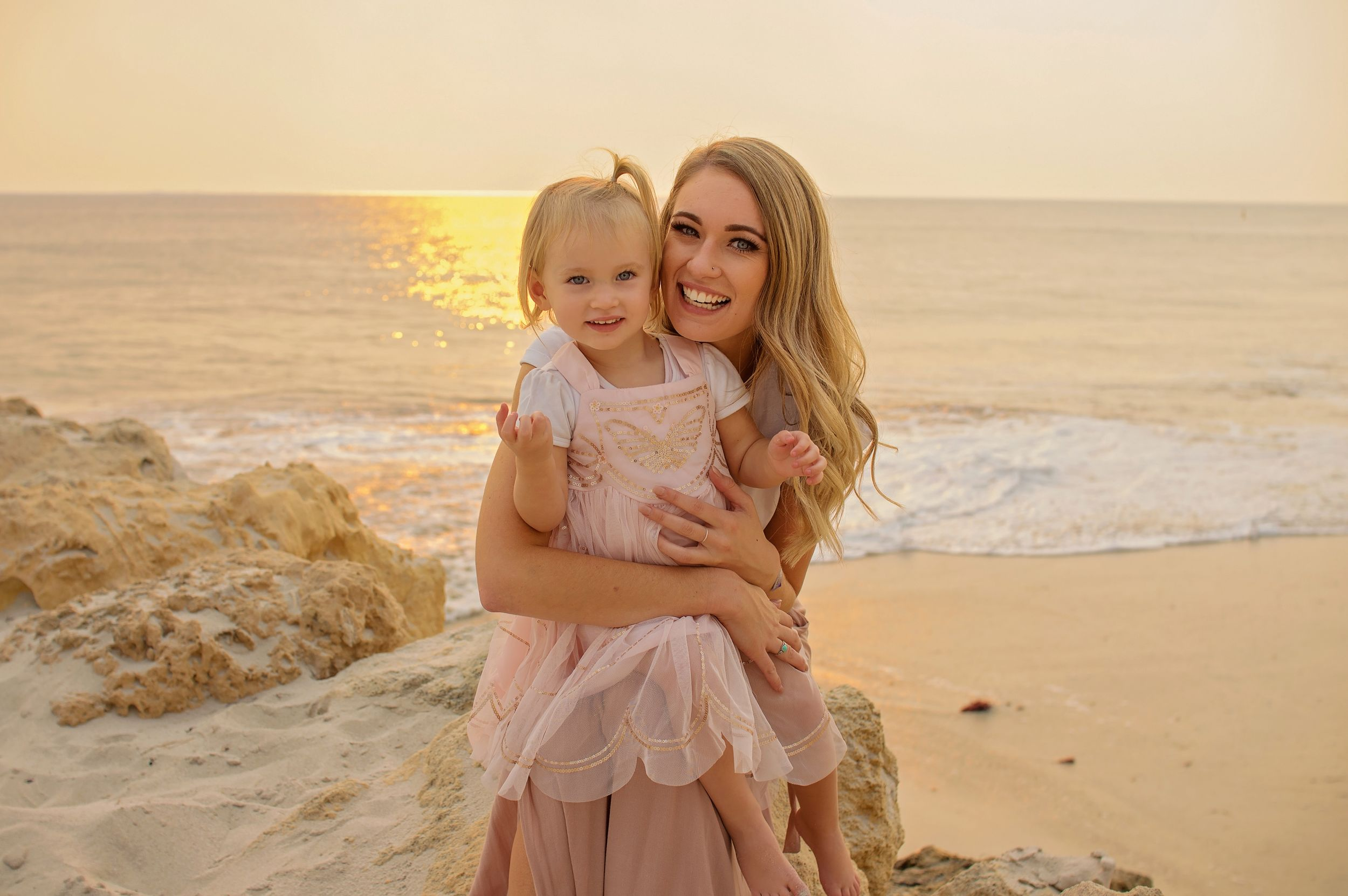 mother holding young daughter on beach smiling with sunset