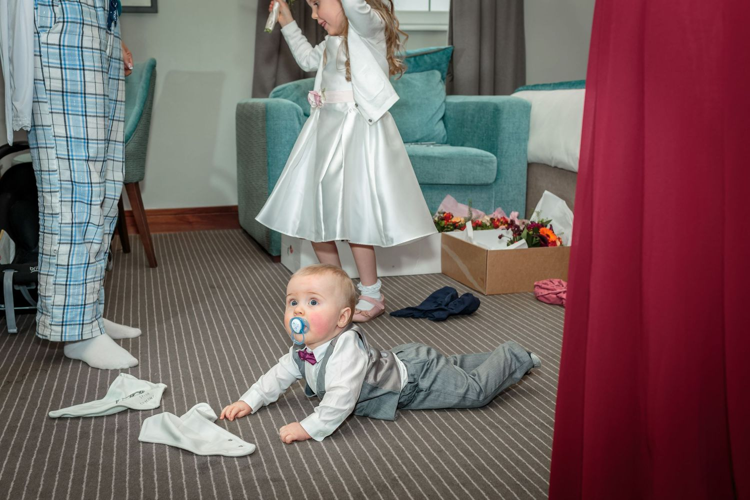 young baby in a shirt and waistcoat lying on his stomach the hotel floor as the bridal prep continue around him