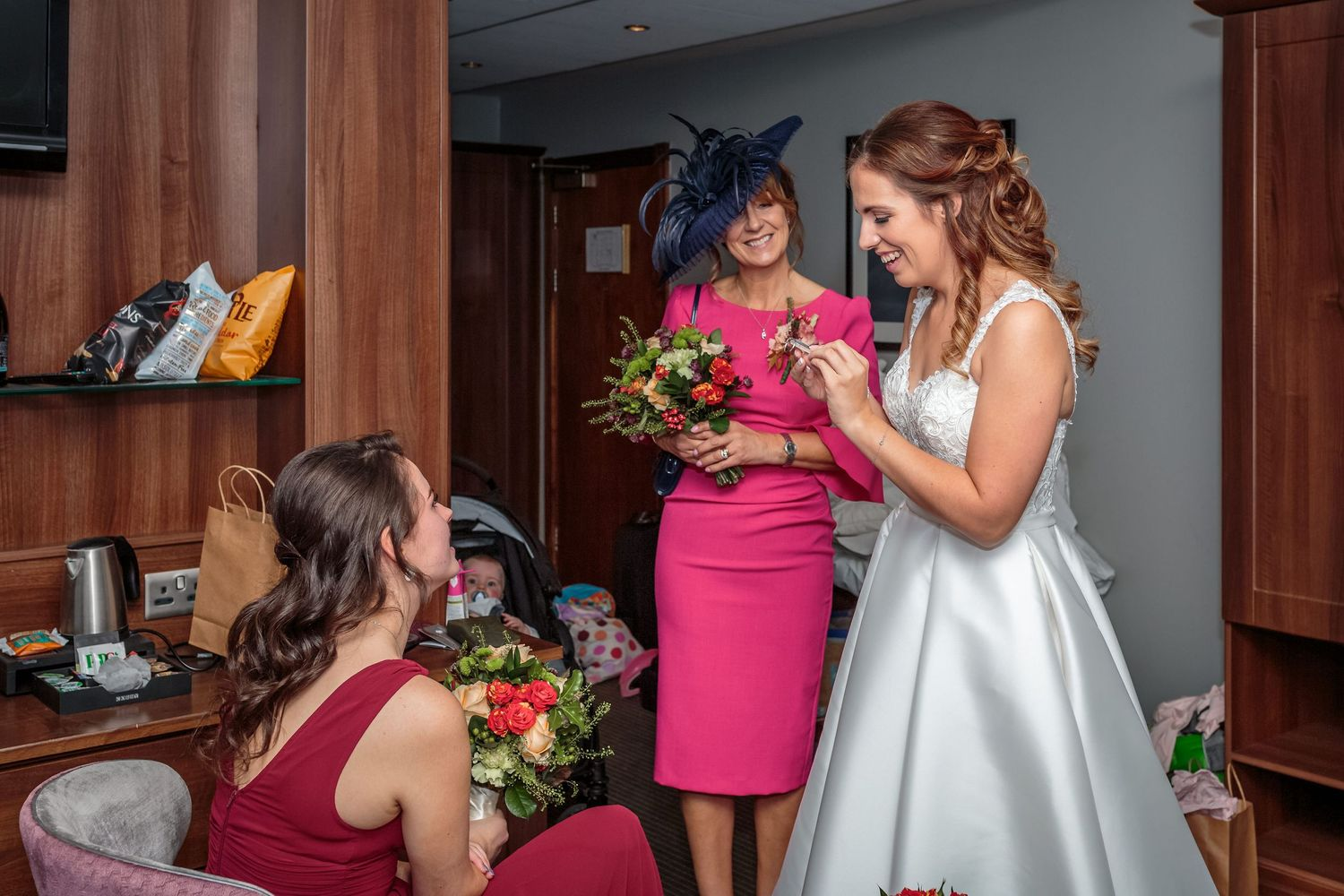 bride looking at a button hole smiling as her mum holds up her bouquet