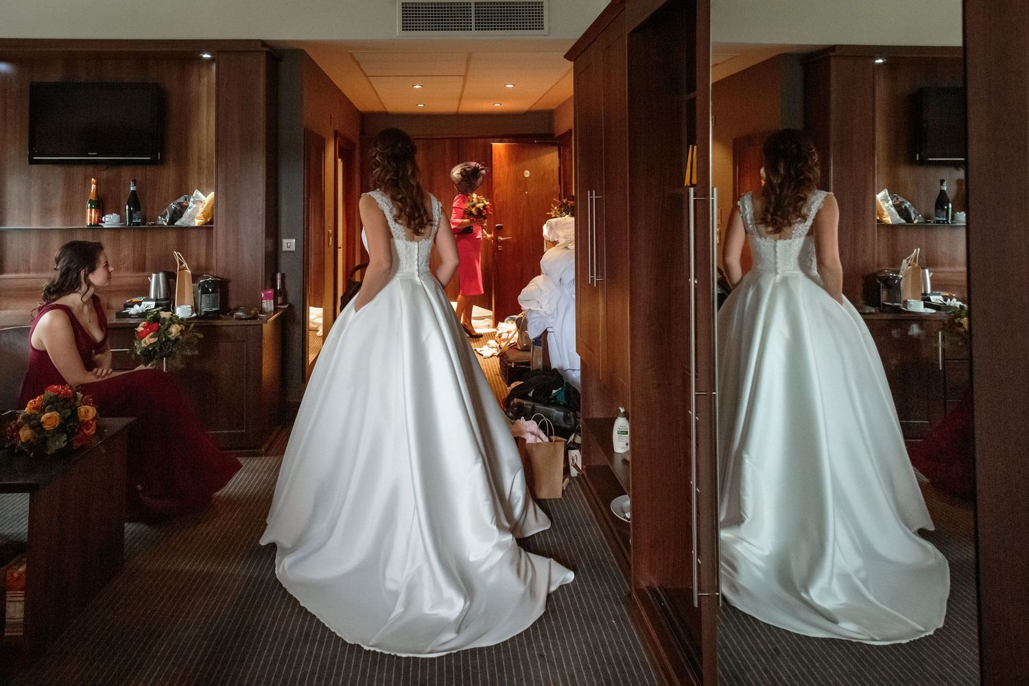 bride with her hands in the pockets pf her wedding dress reflected in the full length wardrobe mirror