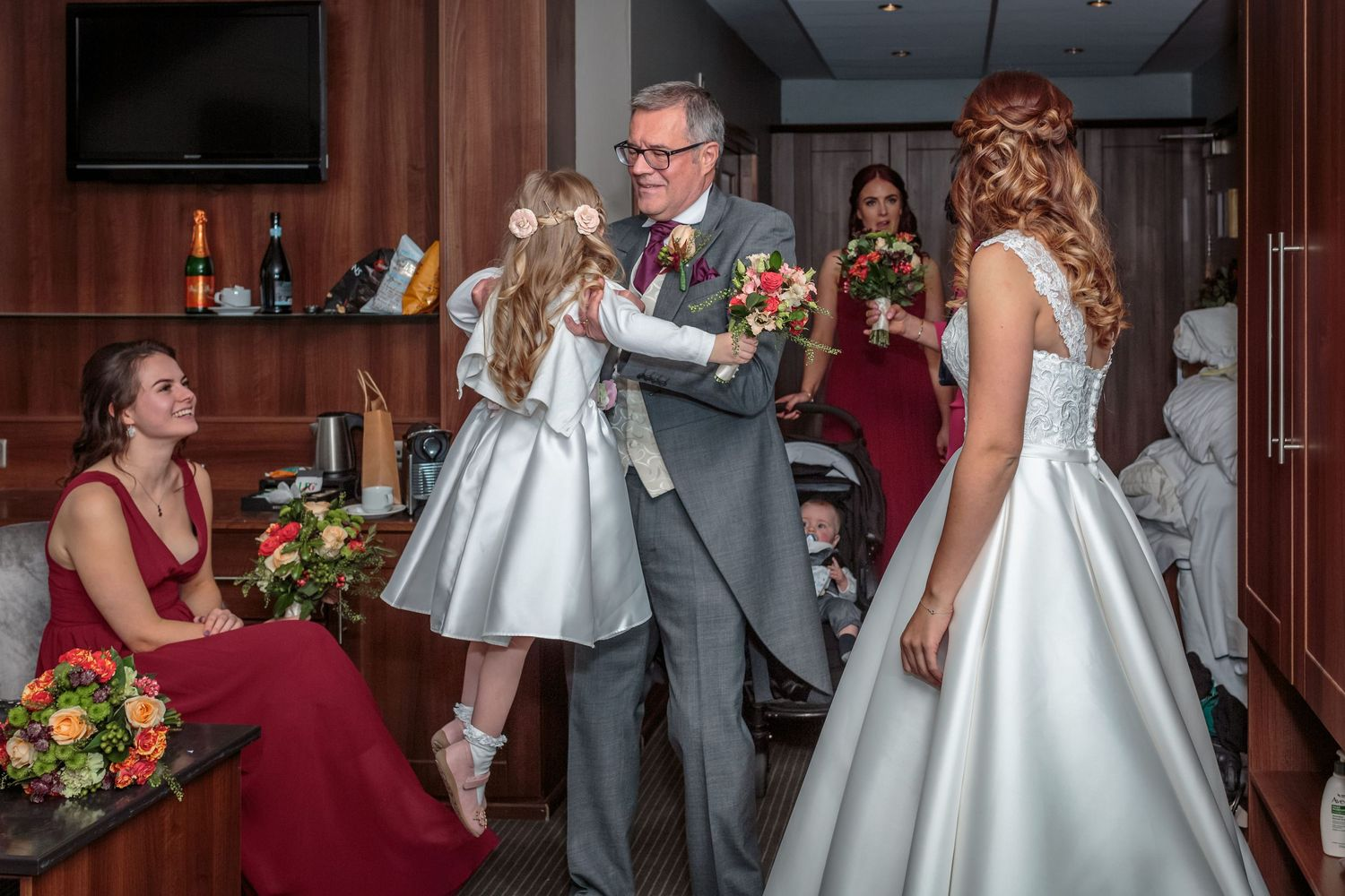 father of the bride lifts up the young flower girl watched by the bride and bridesmaids