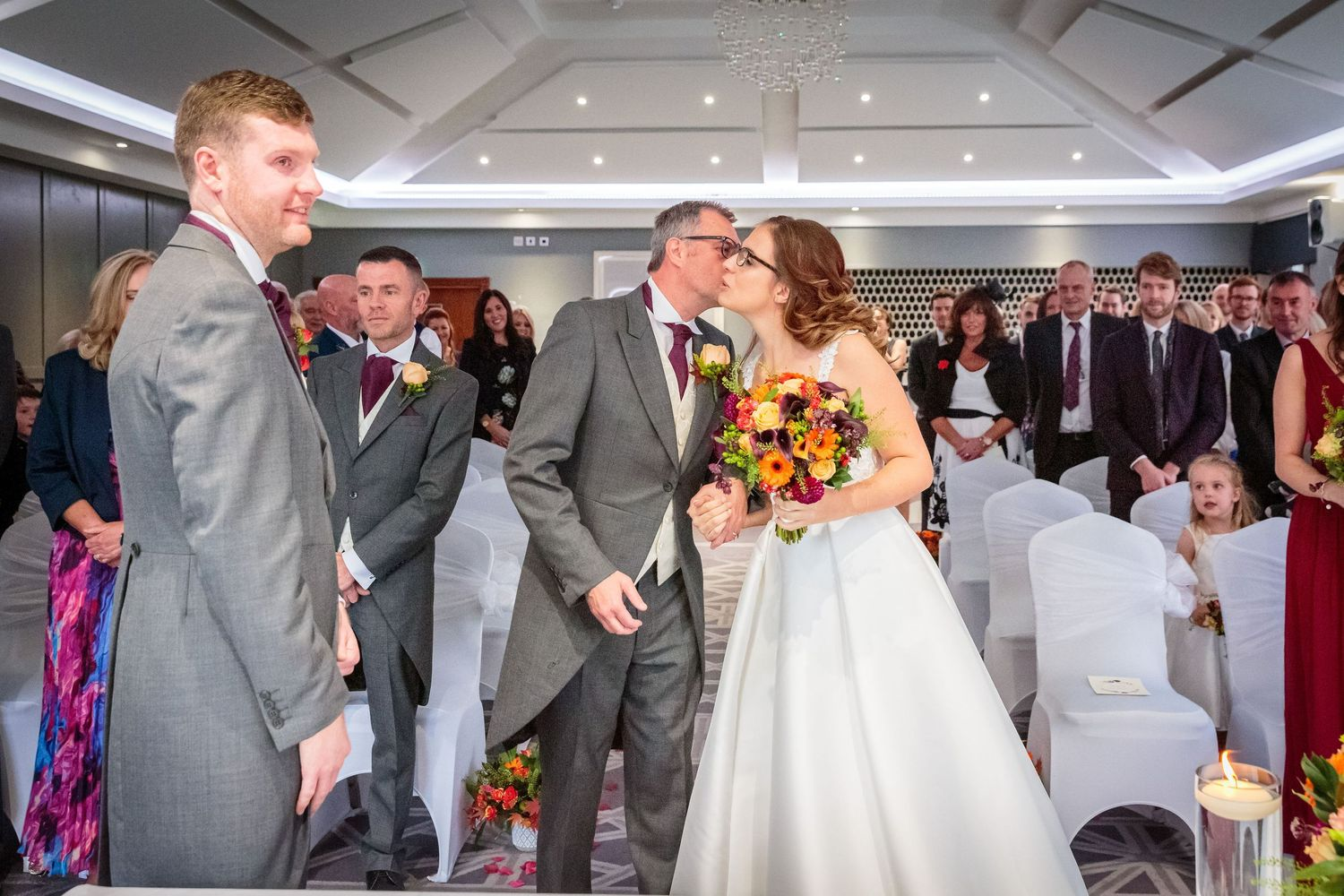 bride gets a kiss on the cheek from her father as they reach the end of the aisle