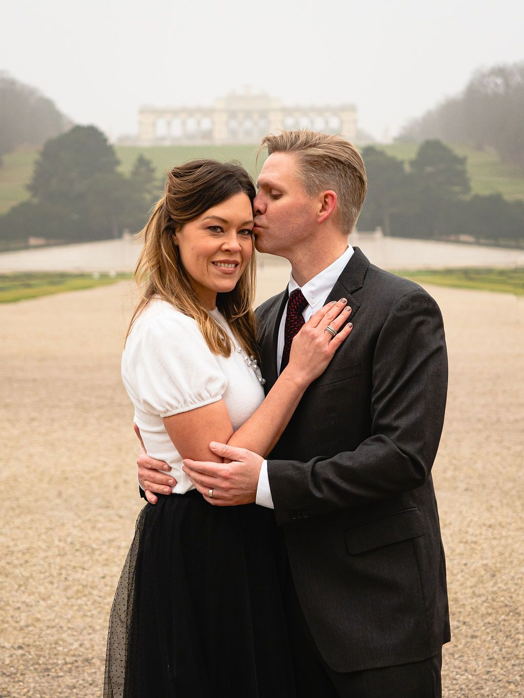 Woman looking at the camera and man is kissing her forehead. Background is the Gloriette in Vienna, Austria