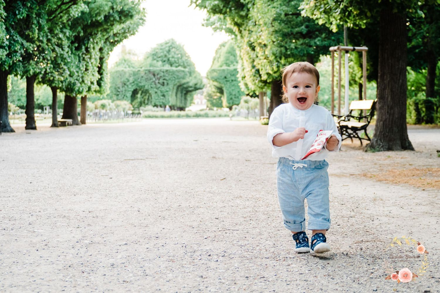 1 year old toddler running thru the Schönbrunn gardens in Vienna wearing a white top and blue trousers.