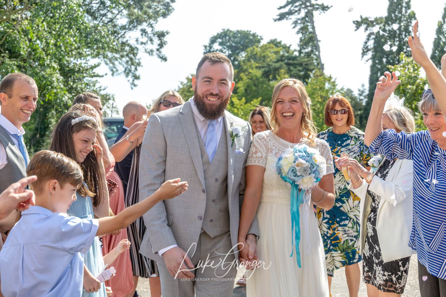 bride and groom just married having photos taken in danson house gardens confetti