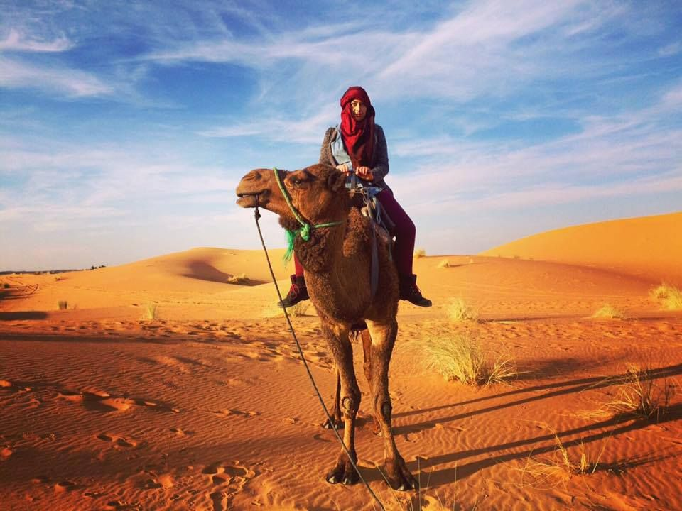 A woman on a camel in Sahara Desert Erg Chebbi Merzouga, Morocco. Sand dunes and sky behind her. She is wearing a hijab