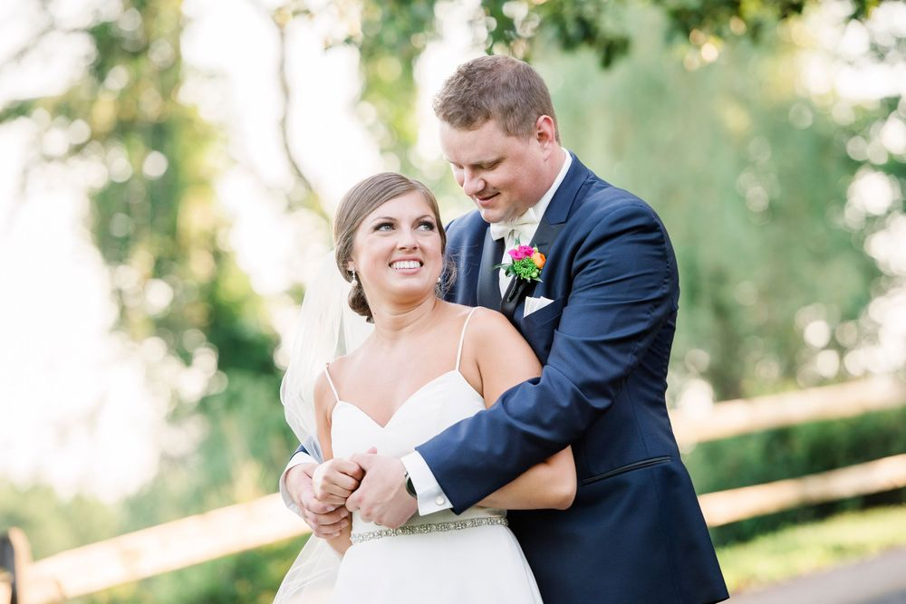 wedding photo of groom with his arms around bride at The Manor House at Commonwealth wedding venue
