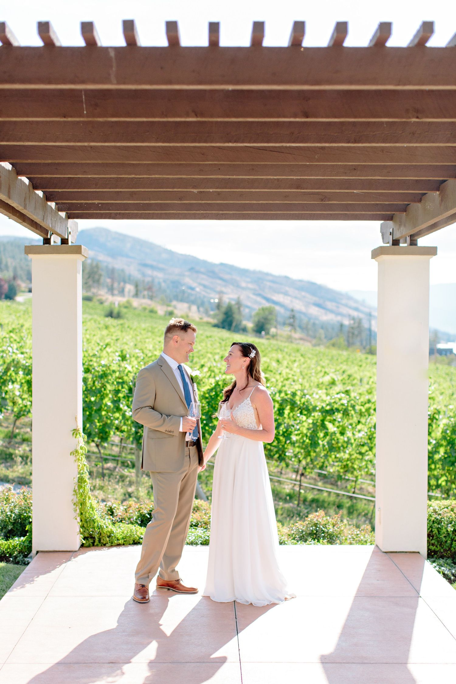 bride and groom under wood pergola CedarCreek Winery