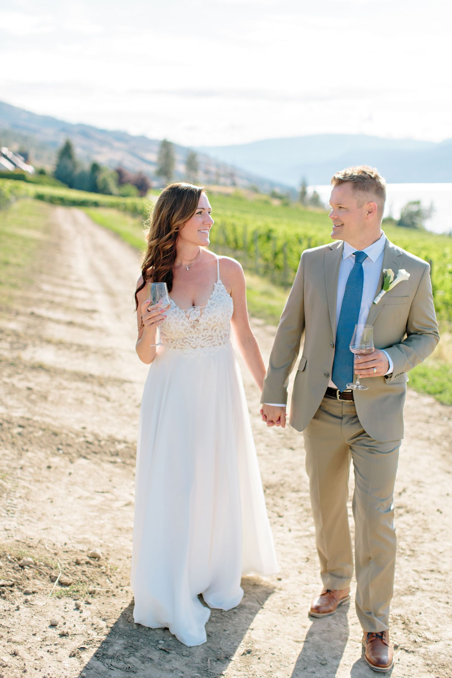 holding hands walking in vineyard