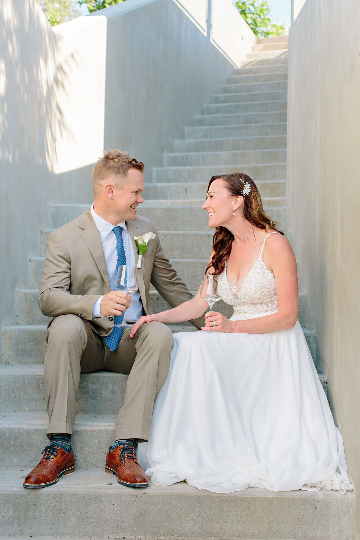 bride and groom sitting on steps at CedarCreek Winery