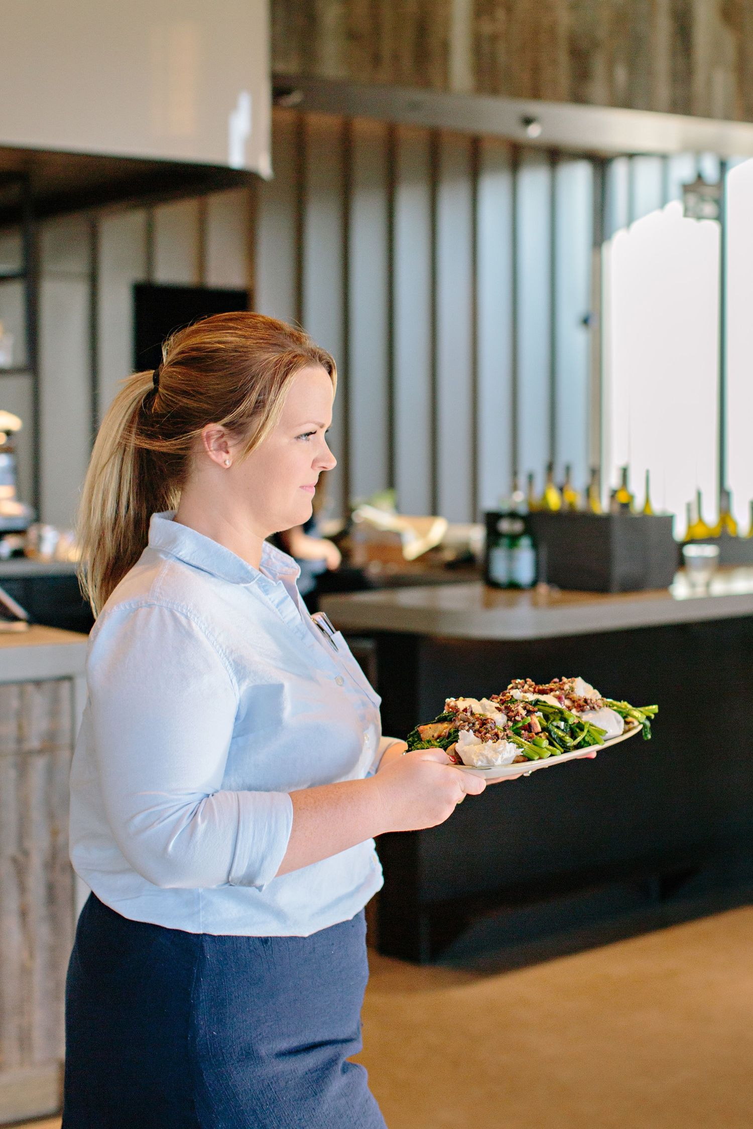 waitress bringing burrata dish to wedding guest