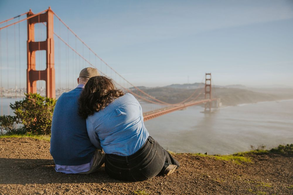 rebecca skidgel photography engagement session in marin headlands couple cuddling in front of golden gate bridge