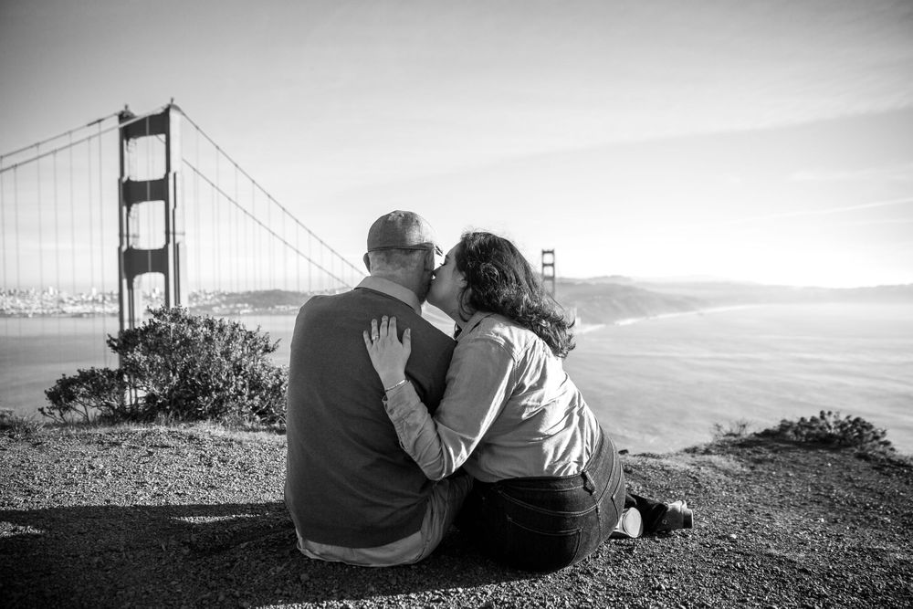 rebecca skidgel photography engagement session in marin headlands couple cuddling golden gate bridge girl kiss guys face
