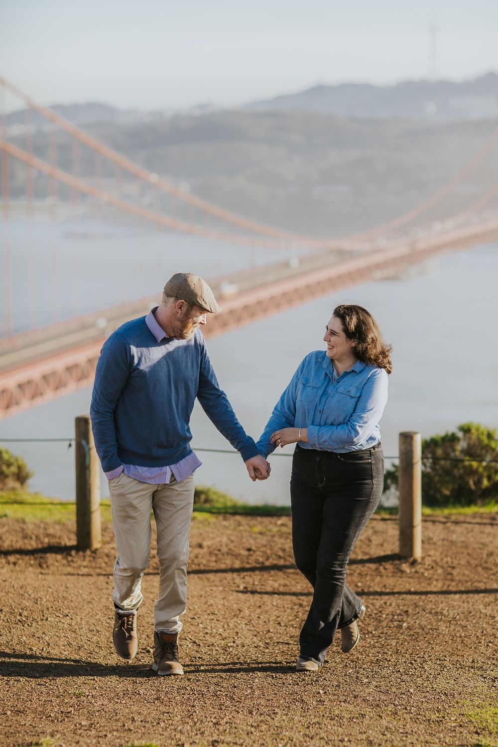 rebecca skidgel photography engagement session in marin headlands holding hands walking laughing golden gate bridge