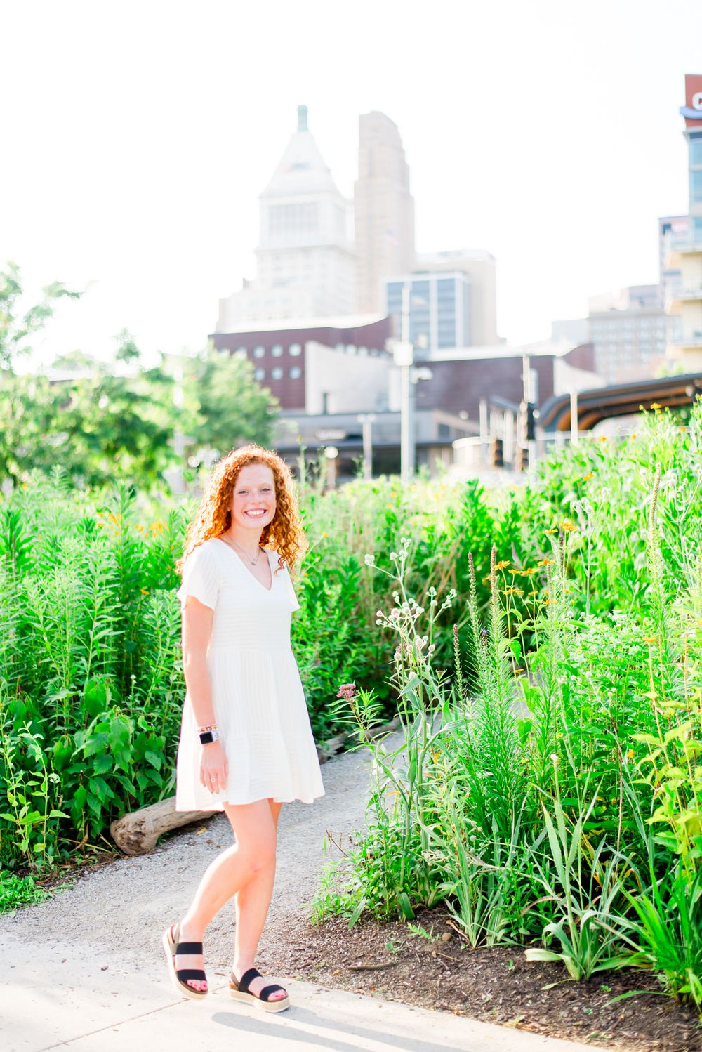 woman with red curly hair in white dress walks through flowers at Smale Park in downtown Cincinnati for senior pictures